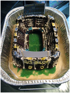 cake shaped and decorated like the University of Michigan football stadium